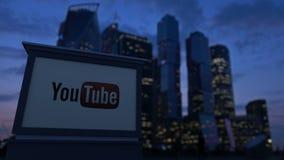 Доска signage улицы с логотипом Youtube в вечере Запачканная предпосылка небоскребов финансового района Редакционное 4K акции видеоматериалы