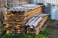 Доски, пиломатериал, который хранят и покрываемые с шифером, лежат в частной зоне в угле загородки стоковые изображения