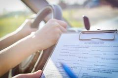 Досмотрщик заполняя в форме дорожного испытания лицензии ` s водителя Стоковые Изображения RF