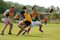 Достигаемости игрока для того чтобы уловить шарик в австралийце управляют футбольной игрой Стоковое Изображение
