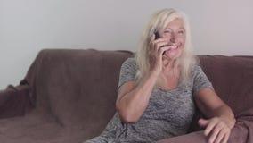 Достигшая возраста выбытая женщина говоря по телефону Портрет бабушки говоря с телефоном и усаживая на софу сток-видео