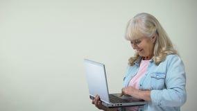 Достигшая возраста дама печатая на ноутбуке показывая большие пальцы руки-вверх, компьютерную грамотность для пенсионеров видеоматериал