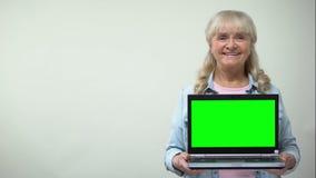 Достигшая возраста дама показывая ноутбук с зеленым экраном, онлайн ходя по магазинам шаблоном скидок видеоматериал
