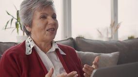 Достигшая возраста женщина говоря на видео- звонке с друзьями видеоматериал