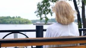 Достигшее возраста женское смотря река, думая о жизни, безмятежность сельской местности, остатки стоковая фотография rf