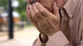 Достигший возраста выбытый конец-вверх человека плача, покрывая сторону с руками в отчаянии, скорба стоковые фотографии rf