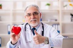 Достигший возраста мужской кардиолог доктора с моделью сердца стоковая фотография rf