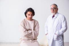 Достигший возраста мужской психиатр доктора рассматривая молодого пациента стоковое фото rf