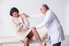 Достигший возраста мужской психиатр доктора рассматривая молодого пациента стоковые фотографии rf