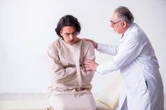Достигший возраста мужской психиатр доктора рассматривая молодого пациента стоковые изображения