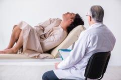 Достигший возраста мужской психиатр доктора рассматривая молодого пациента стоковое изображение rf