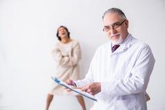 Достигший возраста мужской психиатр доктора рассматривая молодого пациента стоковая фотография rf