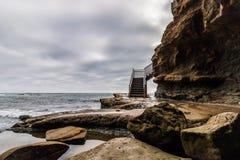 Доступ лестницы серфера к океану на бурный день Стоковые Изображения RF
