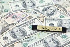 Доход слова на куче банкнот доллара США Стоковое Изображение