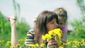 Дочь дает запаху мамы букет одуванчиков сток-видео