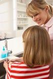 дочь вручает запиток раковины мати кухни Стоковое фото RF