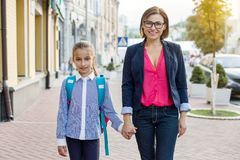дочь вручает маму удерживания Родитель принимает ребенка к школе стоковые фотографии rf