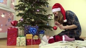 Дочь выставки матери newborn в шарике игрушки ели платья рождества акции видеоматериалы