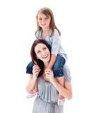 дочь давая ее езду piggyback мати стоковые изображения