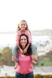 дочь давая ее мати piggyback стоковое изображение rf