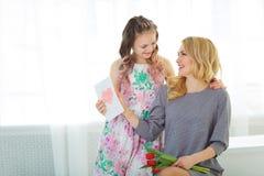 Дочь дала ее матери букет тюльпанов и открытку сделанную с ее собственными руками счастливое материнство Стоковые Фотографии RF
