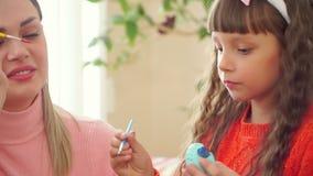 Дочь держит в одной руке яйцо цыпленка, вторую щетку которой она рисует пункт около сидеть мать которая сток-видео