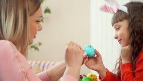 Дочь держит голубое яйцо цыпленка, и моя мать рисует на ей волнистую картину с красной кистью акции видеоматериалы