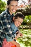 Дочь жизнерадостной матери обнимая в дворе стоковые изображения rf