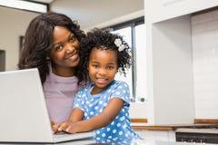 Дочь используя компьтер-книжку с матерью Стоковое Изображение RF