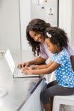 Дочь используя компьтер-книжку с матерью Стоковое Фото
