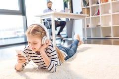 Дочь используя smartphone и наушники, бизнесмена работая позади в офисе Стоковое Изображение RF