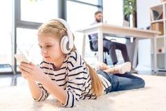 Дочь используя smartphone и наушники, бизнесмена работая позади в офисе Стоковые Фото