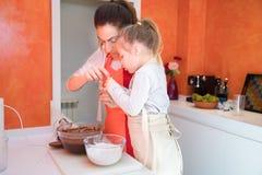 Дочь и мать варя торт совместно в кухне Стоковые Изображения