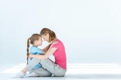Дочь и мать обнимая один другого на белизне Стоковое Фото