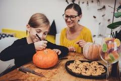 Дочь и мать создавая Джек-O-фонарик Стоковые Фотографии RF