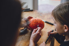Дочь и мать создавая Джек-O-фонарик Стоковая Фотография