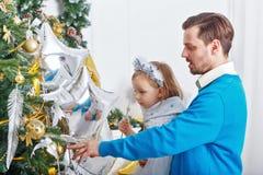 Дочь и отец украшают рождественскую елку Стоковая Фотография