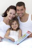 дочь кровати parents чтение портрета Стоковое Изображение RF