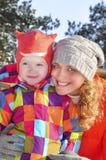 Дочь мамы и младенца в снежном лесе. Стоковое Фото