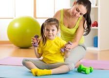 Дочь мамы и ребенка приниматься гантели фитнеса Стоковое Изображение