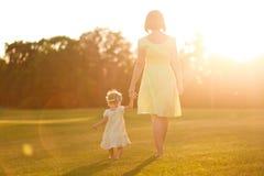 Дочь мамы одевает босоногий заход солнца травы рук ног Стоковые Изображения RF