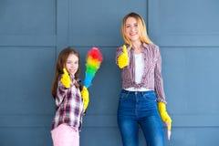 Дочь мамы thumbs вверх по чистым домашним рутинным работам по дому стоковое изображение rf