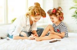 Дочь матери и ребенка в curlers волос красит ногти, делает pedi Стоковая Фотография