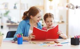 Дочь матери и ребенка делая сочинительство домашней работы и читая дома стоковые изображения