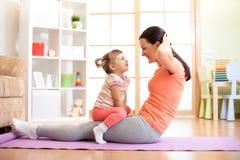 Дочь матери и ребенка приниманнсяый за фитнес, йога, работает дома Пресса качания ребенк и женщины на животе Стоковое Фото