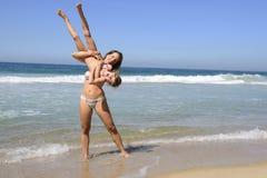 Дочь матери поднимаясь вверх на пляже стоковое фото rf