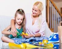 Дочь матери уча, который нужно зашить стоковые изображения