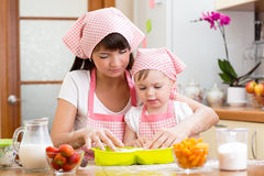 Дочь молодой женщины и ребенк делая ягода плодоовощ испечь стоковые фото