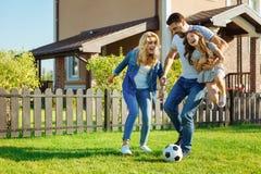 Дочь нося любящего отца и футбол играть с семьей Стоковая Фотография RF
