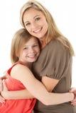 дочь обнимая детенышей студии портрета мати стоковые фотографии rf